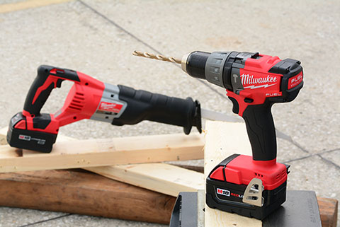 Red and black electric saw and drill on top of wooden boards