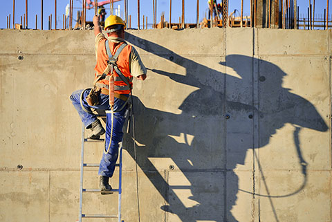 Man in a hard hat wears a safety harness while climbing a ladder that leans against a large concrete block wall