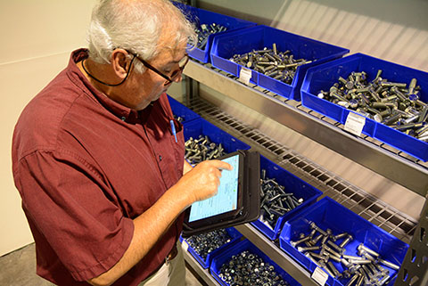 A-Jax employee uses a digital pad to log quantities of fasteners at a client's site