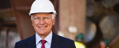 Company executive in a suit and tie and wearing a hard hat