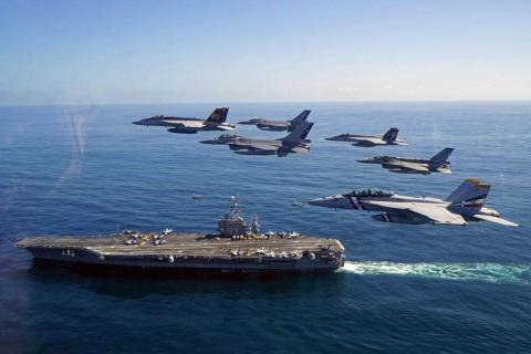 Naval jet fighters fly above an air craft carrier